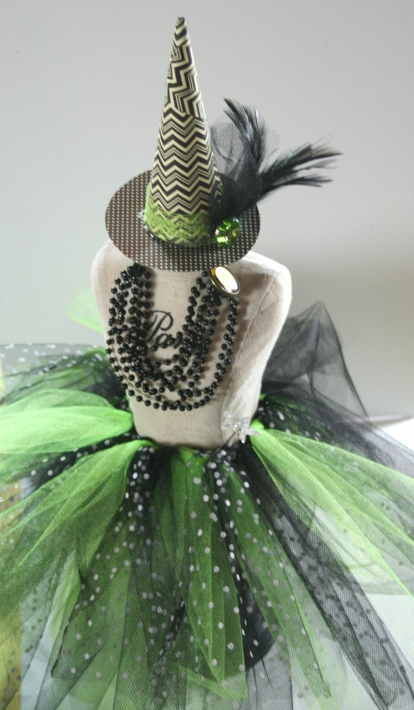 mini dressform decorated with beads, tulle, ribbon, feathers, bling, hat, skirt, and necklace for Halloween to look like a cute home decor witch