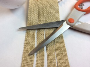 cutting burlap ribbon into strips for diy acorn ornament tutorial